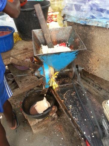 Grinding beans for akara in the market