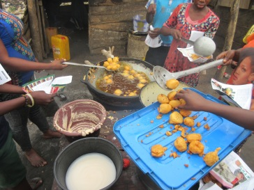 Akara being removed from oil and packed into newspaper